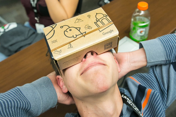 """Arrowhead Park Early College High School freshman Zach Dickens, 15, foreground, kicks his heels up while using the GOOGLE virtual reality headset on Tuesday, Feb. 9, 2016, in class with his classmates. APECHS was the first school in the state of New Mexico to have been selected to be part of the GOOGLE Expeditions Pioneer program. The students were viewing various locations including space, a volcano, and foreign countries. """"It was nice,"""" said Dickens, """"a little bit uncomfortable with glasses but still very nice."""" (AP PHOTO/Las Cruces Sun-News)"""