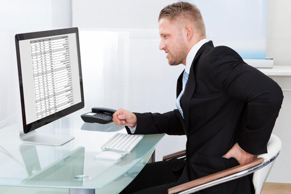 man-in-black-suit-sitting-at-computer-with-lower-back-pain