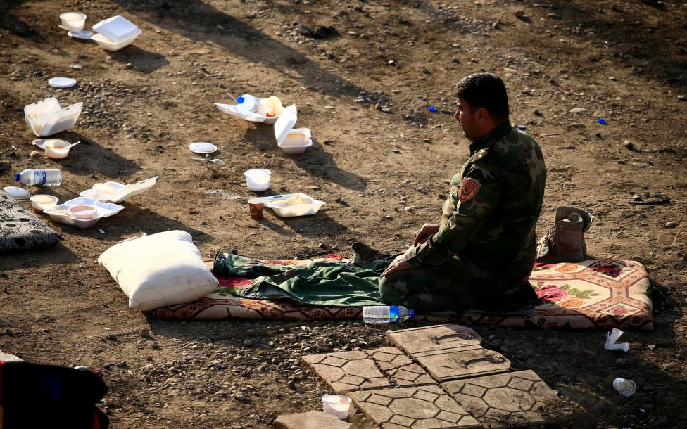 A member of Peshmerga forces pray in the town of Bashiqa, east of Mosul