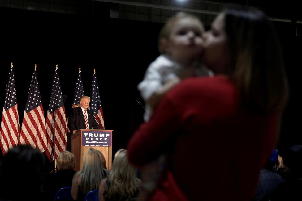 A woman kisses her son as Republican presidential nominee Donald Trump speaks at a campaign event in Aston