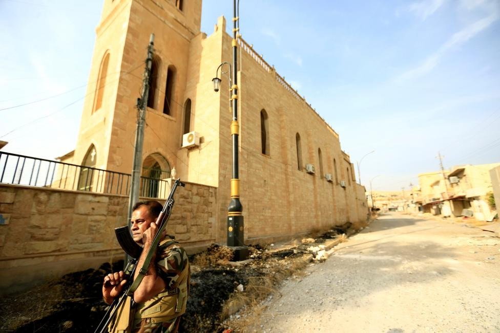 A member of Peshmerga forces stands outside the Mart Shmoni Church since it was recaptured from the Islamic State in the town of Bashiqa