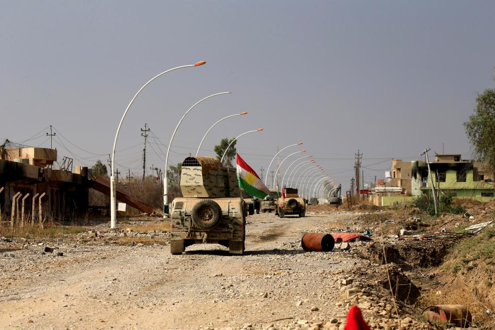Military vehicles of Peshmerga forces drive in the town of Bashiqa, east of Mosul, during an operation to attack Islamic State militants in Mosul