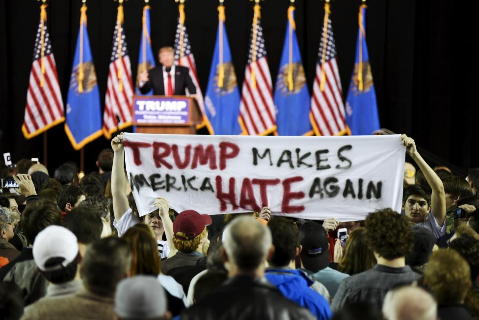 Protestors hold up a sign towards the crowd at a rally for U.S. Republican presidential candidate Donald Trump at Oral Roberts University in Tulsa, Oklahoma