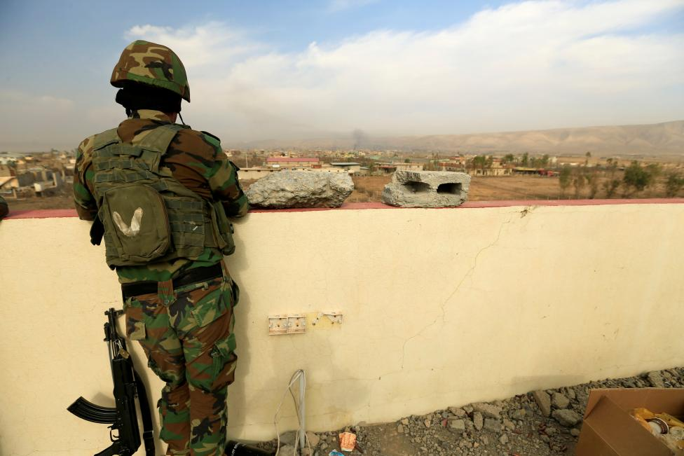 A member of Peshmerga forces stands on a building in the town of Bashiqa, east of Mosul