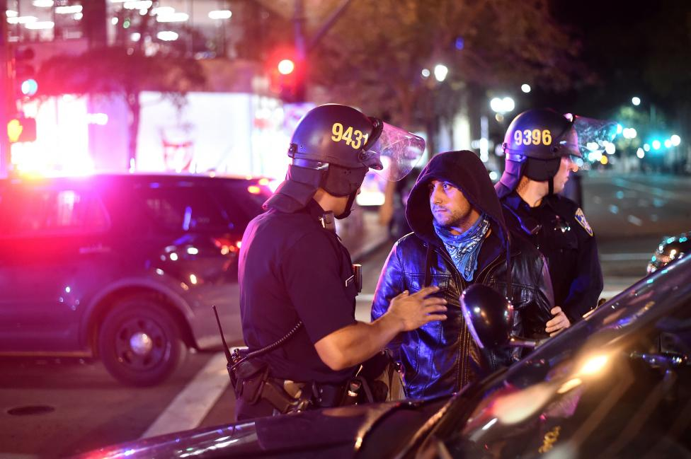 Police detain a protester marching against president-elect Donald Trump in Oakland