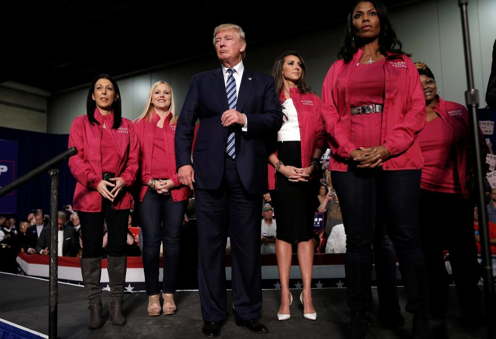 Republican U.S. presidential nominee Donald Trump stands with female supporters on stage at a campaign rally in Charlotte