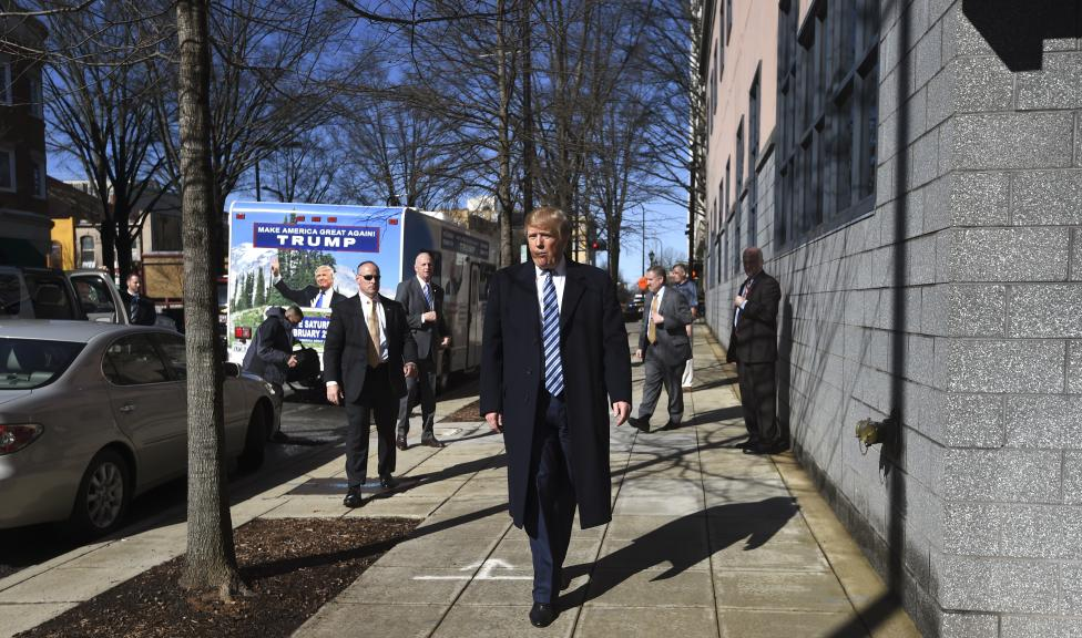 Republican U.S. presidential candidate Trump walks down the street as he arrives at his campaign headquarters in Greenville, South Carolina
