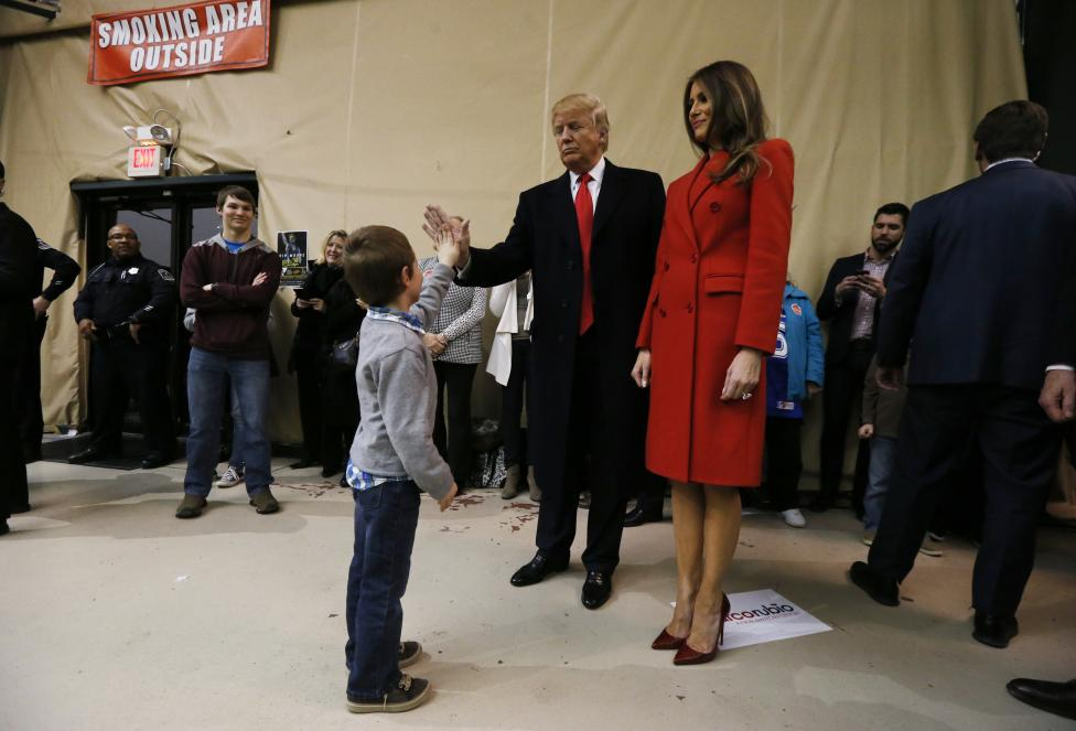 A young boy high-fives Republican Presidential candidateTrump at 7 flags event center in Clive, Iowa