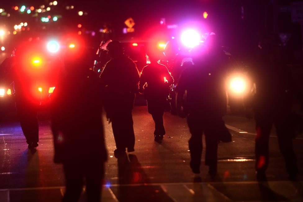 Oakland police officers chase a group of about 50 protesters against president-elect Donald Trump in Oakland