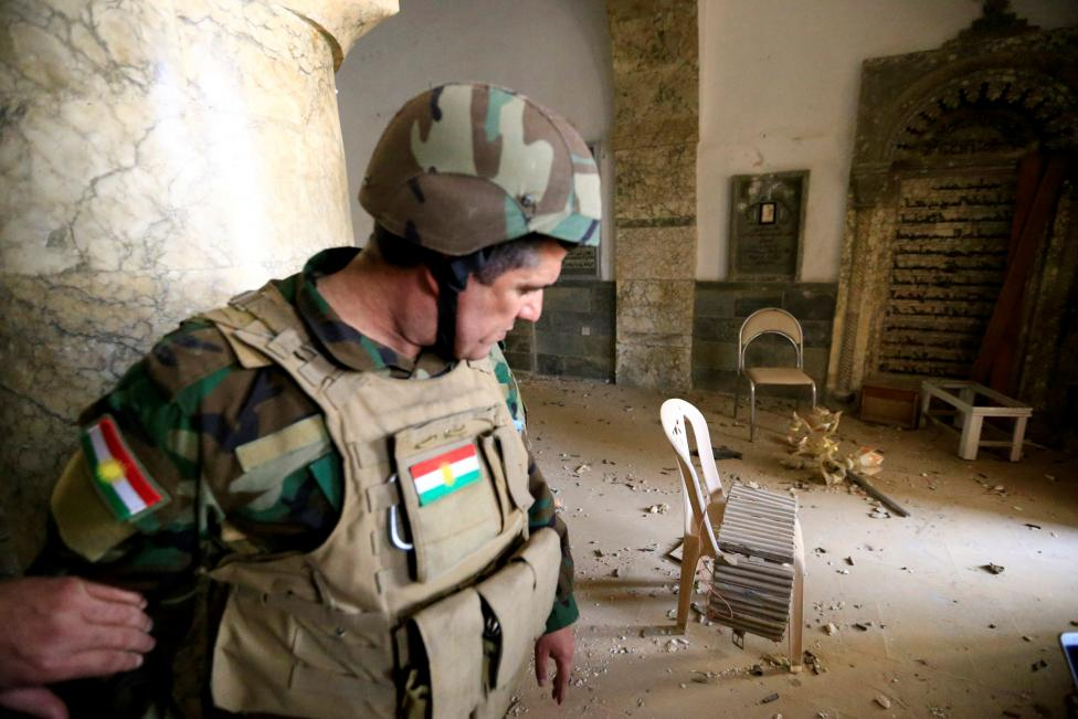 A member of Peshmerga forces inspects the Mart Shmoni Church since it was recaptured from Islamic State in the town of Bashiqa