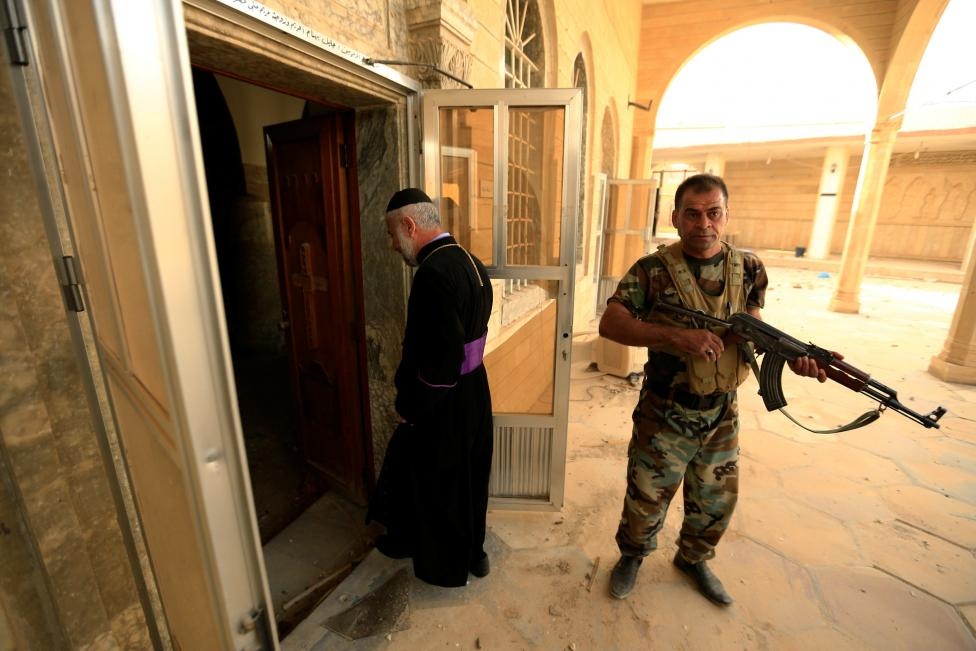 Priests with Peshmerga forces inspect the Mart Shmoni Church since it was recaptured from the Islamic State in the town of Bashiqa