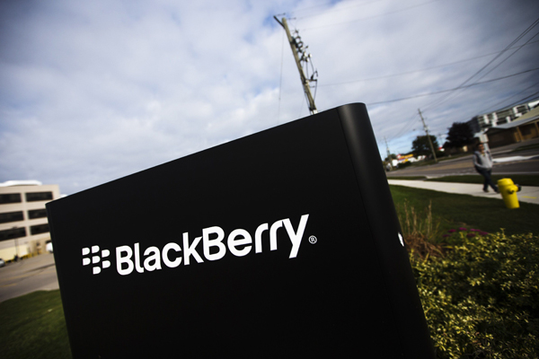 A man walks by a Blackberry sign at the Blackberry campus in Waterloo, September 23, 2013. Struggling smartphone maker BlackBerry on Monday signed a tentative deal to be acquired by a consortium led by its biggest shareholder, setting a $4.7 billion floor in the auction of the Canadian company that invented on-the-go email.   REUTERS/Mark Blinch (CANADA - Tags: BUSINESS SCIENCE TECHNOLOGY)